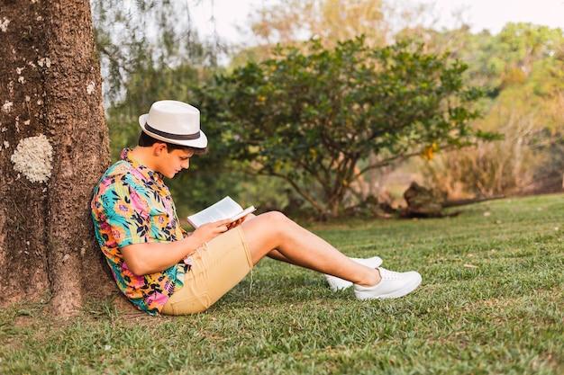 帽子と花柄のシャツを着た観光客は、公園で本を読みます。木に横たわっている男が本を読みます。熱帯の男が本を読みます。リラクゼーションとアウトドアのコンセプト。