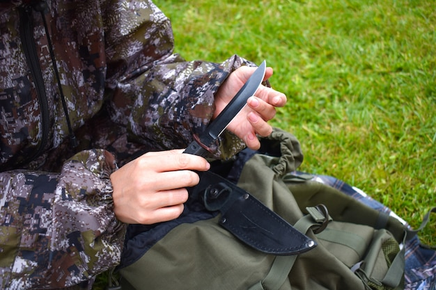 Tourist with a hunting sharp knife in  hands outdoor