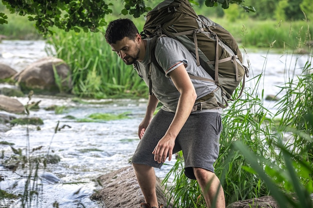 A tourist with a large hiking backpack is cooling off near a mountain river in the summer heat.