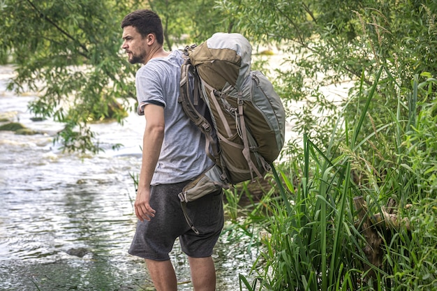A tourist with a large hiking backpack near a mountain river in the summer heat.