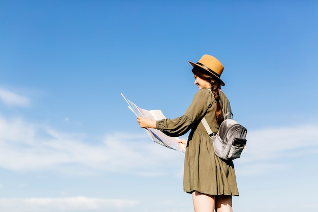 Tourist with map on sunny sky background