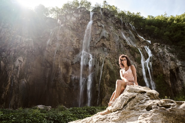 A tourist woman at the big waterfall in plitvice national park, croatia