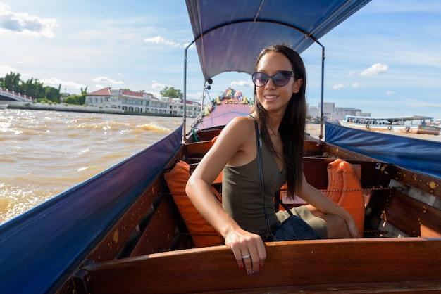 Туристическая женщина, изучающая город бангкок на речной лодке