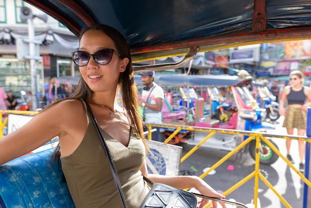 トゥクトゥクタクシーでバンコクの街を探索する観光客の女性