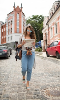 Tourist woman in fashionable sunglasses and newspaper in her hands.