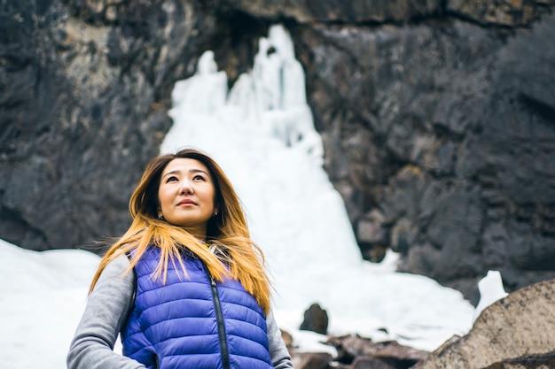 Tourist woman and frozen waterfall