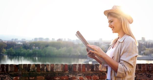 目的地に旅行する旅行者マップを保持している観光客の女性