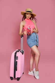 ピンクの背景に新鮮な飲み物とスーツケースを保持している夏のカジュアルな服を着た観光客の女性