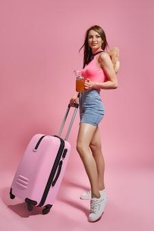ピンクの背景にスーツケースを保持している夏のカジュアルな服の観光客の女性