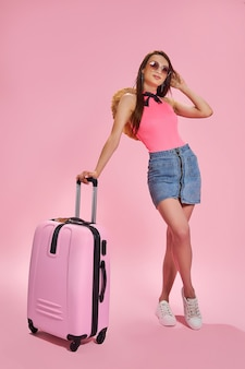 Туристическая женщина в летней повседневной одежде держит чемодан на розовом фоне