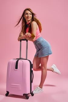 クレジットカードを保持しているピンクの背景に夏のカジュアルな服を着た観光客の女性