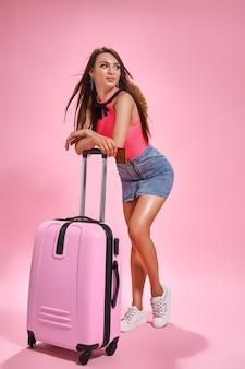Туристическая женщина в летней повседневной одежде на розовом фоне держит кредитную карту