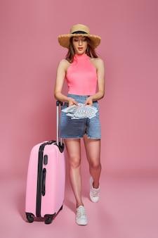 ピンクの背景にお金とスーツケースの札束を保持している夏のカジュアルな服の麦わら帽子の観光客の女性