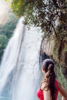 Туристская женщина в водопаде thi lo su в национальном парке в таиланде. глубокий лес красивой природой. треккинг и рафтинг в азии.