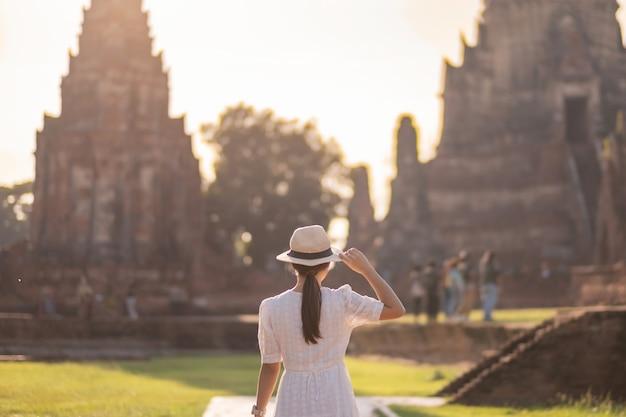アユタヤ歴史公園、夏、アジア、タイの旅行コンセプトのワットチャイワタナラム寺院の古代の仏舎利塔を訪れる白いドレスを着た観光客の女性