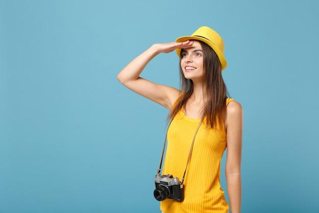 Туристическая женщина в желтой летней повседневной одежде и шляпе с фотоаппаратом на синем