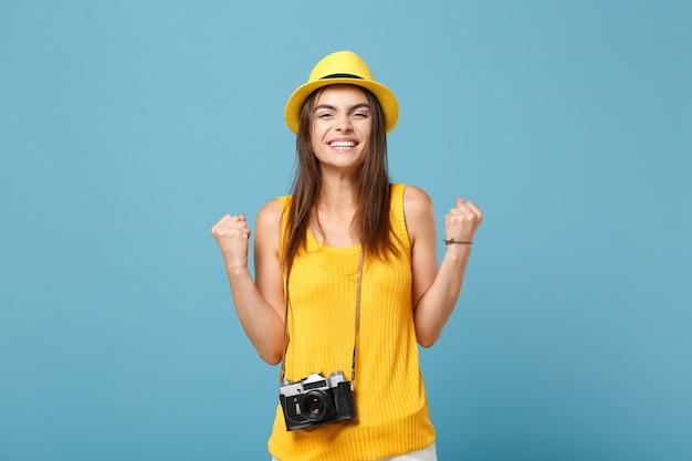 青の写真カメラと黄色の夏のカジュアルな服と帽子の観光客の女性