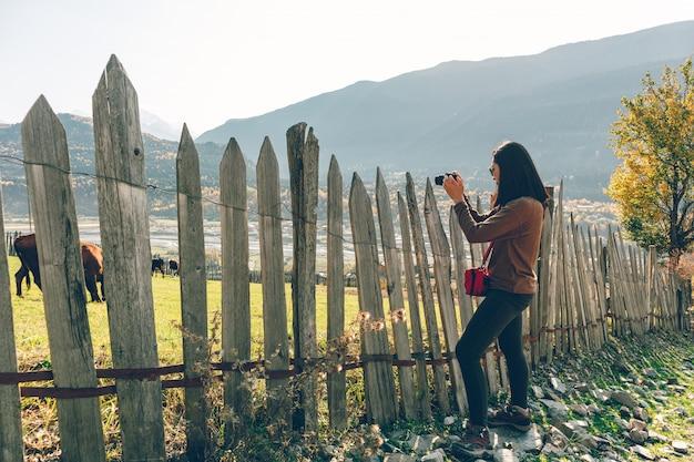 観光客の女性がフェンスを越えて農村の農場の風景写真を取っています。