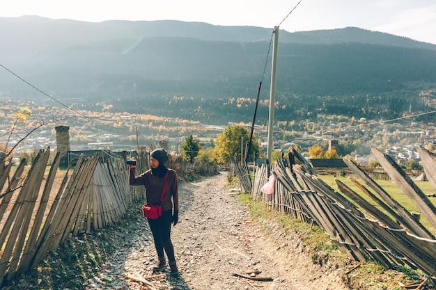 観光女性は小さな田舎町の上の丘で写真を撮っています。