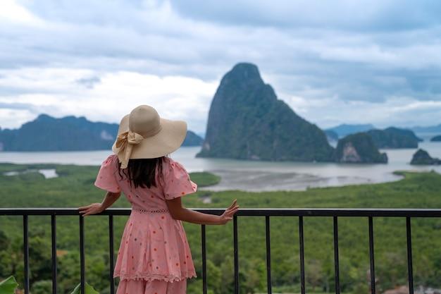 Phang nga의 samed nangshe 관점에서 아름다운 산 섬의 전망을 바라보는 관광 여성