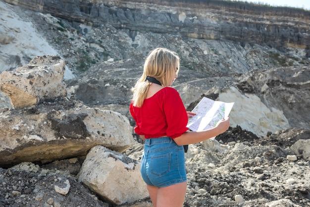 観光客の女性はカメラで石の間で地図を見る