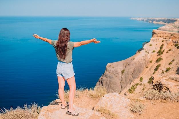 Туристическая женщина открытый на краю побережья скалы