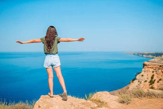 절벽 해변의 가장자리에 야외 관광 여자