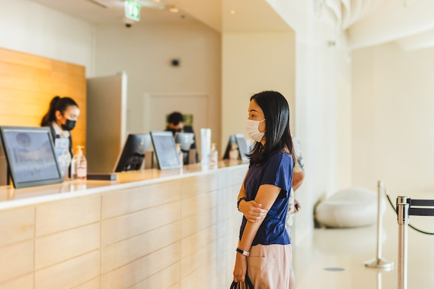 Tourist woman and receptionist at hotel counter wearing medical mask against virus.