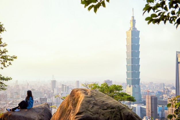 Tourist woman sit on giant stone with 101 tower at sunset