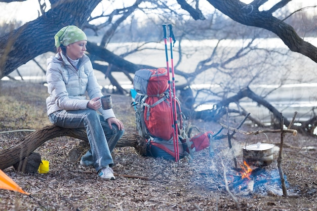 Tourist woman sits at the camp in the forest and mountains