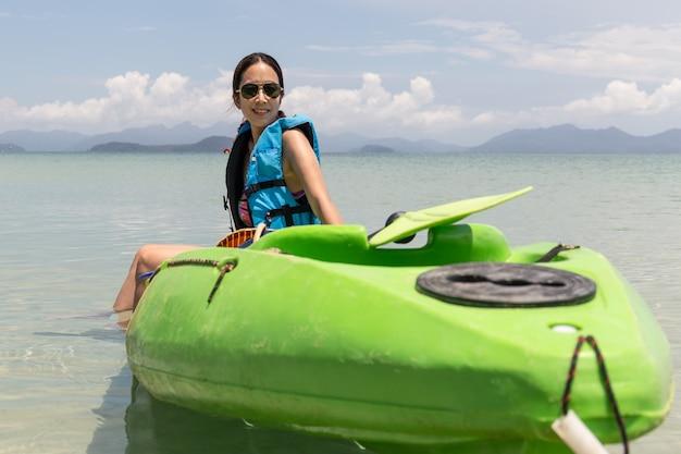 休暇中に美しい熱帯のビーチでカヤックlookignに座っている観光女性。