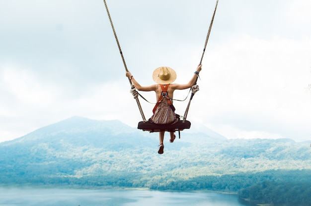 Tourist woman on a swing at vacation in bali, indonesia Premium Photo