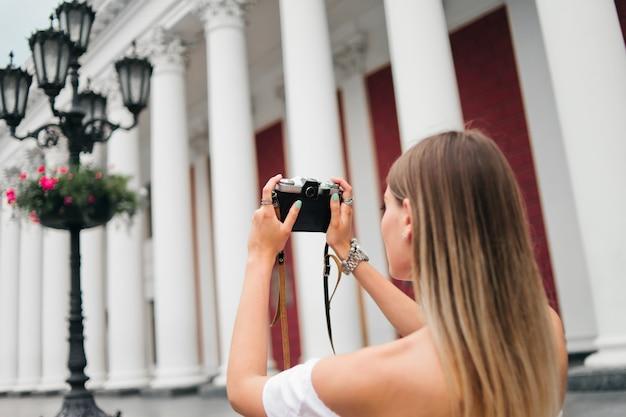 Туристка фотографирует здание с колоннами на ретро-камеру на открытом воздухе