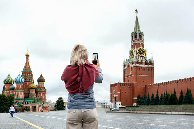 Туристическая женщина фотографирует на своем смартфоне на красной площади в москве, россия.