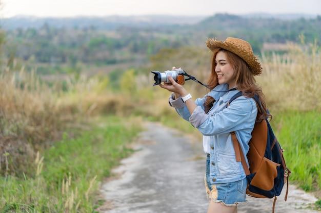 Туристская женщина принимая фото с ее камерой в природе