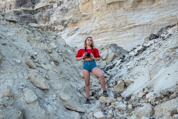 砂漠の谷と岩の写真を撮る観光客の女性。自然を探る