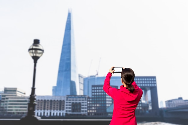 Tourist woman taking picture of building and river thames with cell phone.