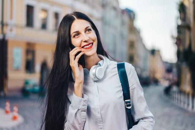 旧市街の通りを散歩を楽しんで、彼女の携帯電話で話しているバックパックを持つ観光客の女性