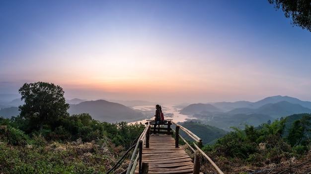 배낭을 가진 관광 여성 스마트 폰 사용 사진 촬영 태국 sangkhom 지구 banmuang village에서 mekong 강 일출