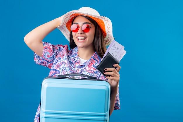 彼女の帽子に触れる幸せと肯定的な顔に笑顔で旅行スーツケースとチケットとパスポートを保持している赤いサングラスをかけた帽子を持つ観光女性