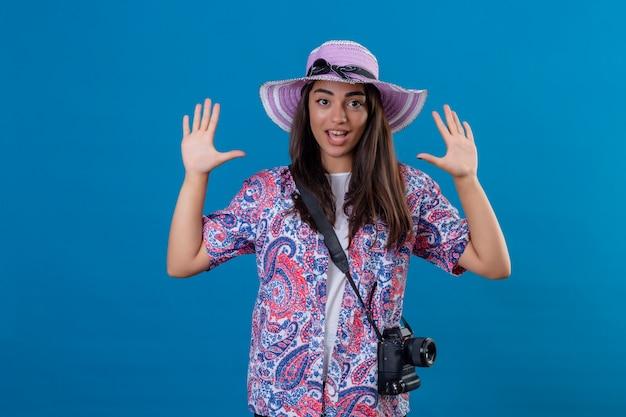 降伏探して手を上げて写真カメラで帽子の観光女性驚いて孤立した青の上に立って
