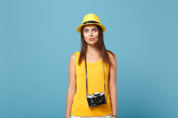 Tourist woman in yellow summer casual clothes and hat with camera on blue