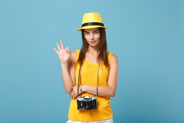 Tourist woman in yellow summer casual clothes and hat with photo camera on blue