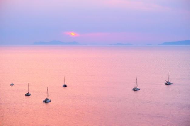 Лодка туристических яхт в эгейском море недалеко от острова санторини с туристами, смотрящими на закат с ...