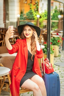 Tourist young caucasian woman in a red jacket and black hat with suitcase takes a selfie on a city