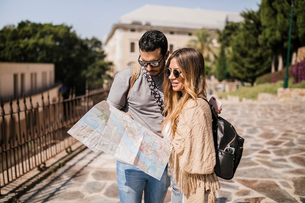 Tourist young couple standing on street looking at map
