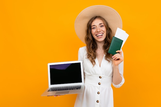 Tourist young girl holds passport in hand and looks at tickets on a laptop over yellow