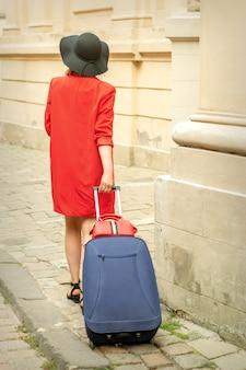 旧市街の通りを旅行しているスーツケースを引っ張る黒い帽子の観光客の若い女性