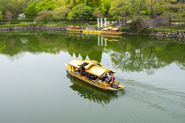 Touristic boats with tourists along the moat of osaka castle