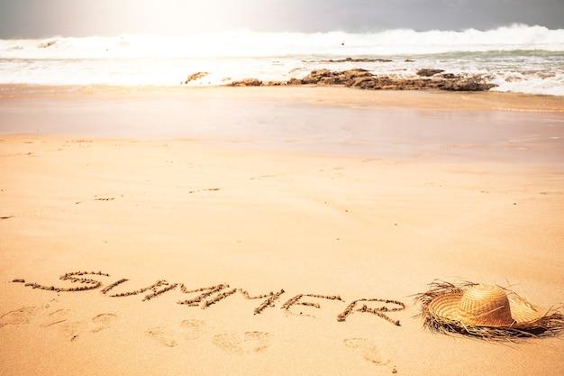 작성 된 모래와 단어 여름에 여행 모자